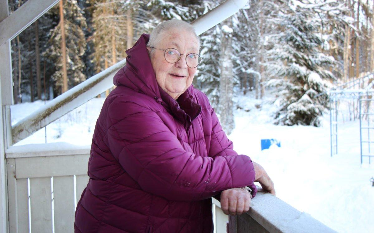 80-åriga Vita Pedersen har problem med att ta sig fram i området eftersom snöplogning och halkbekämpning inte fungerar. På bilden står hon lutad mot sitt trappräcke.