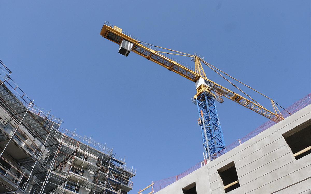Bilden visar en byggarbetsplats med en byggkran mot en blå himmel.