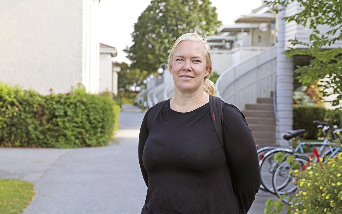 Hanna Hagström står på en gång i bostadsområdet. En trapp skymtar i bakgrunden.
