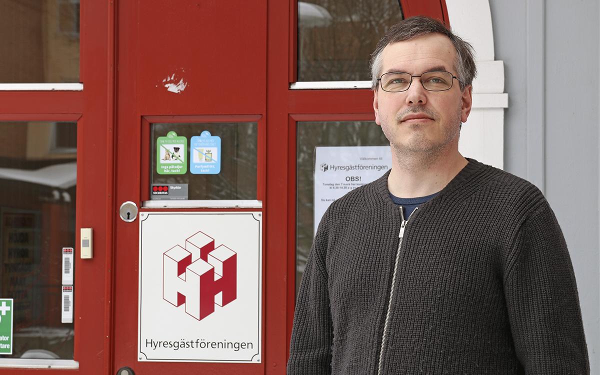 Marcus Kjellin i en brun tröja med blixtlås. Han står utanför en röd dörr där Hyresgästföreningens logga syns