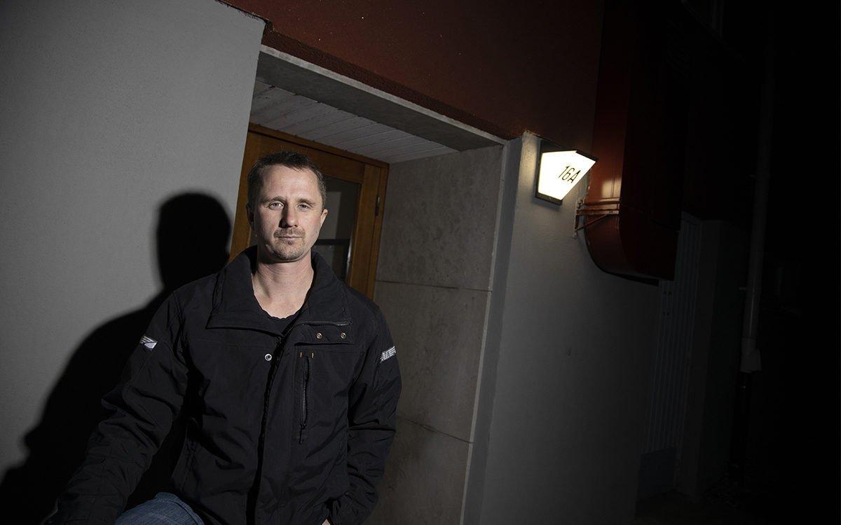 Stefan Helmersson utanför sin port på Simpbylevägen i Norrtälje. Han har på sig en svart jacka. Det är mörkt och ljuset faller på honom från nummerskylten som är en lampa och från kamerablixten.