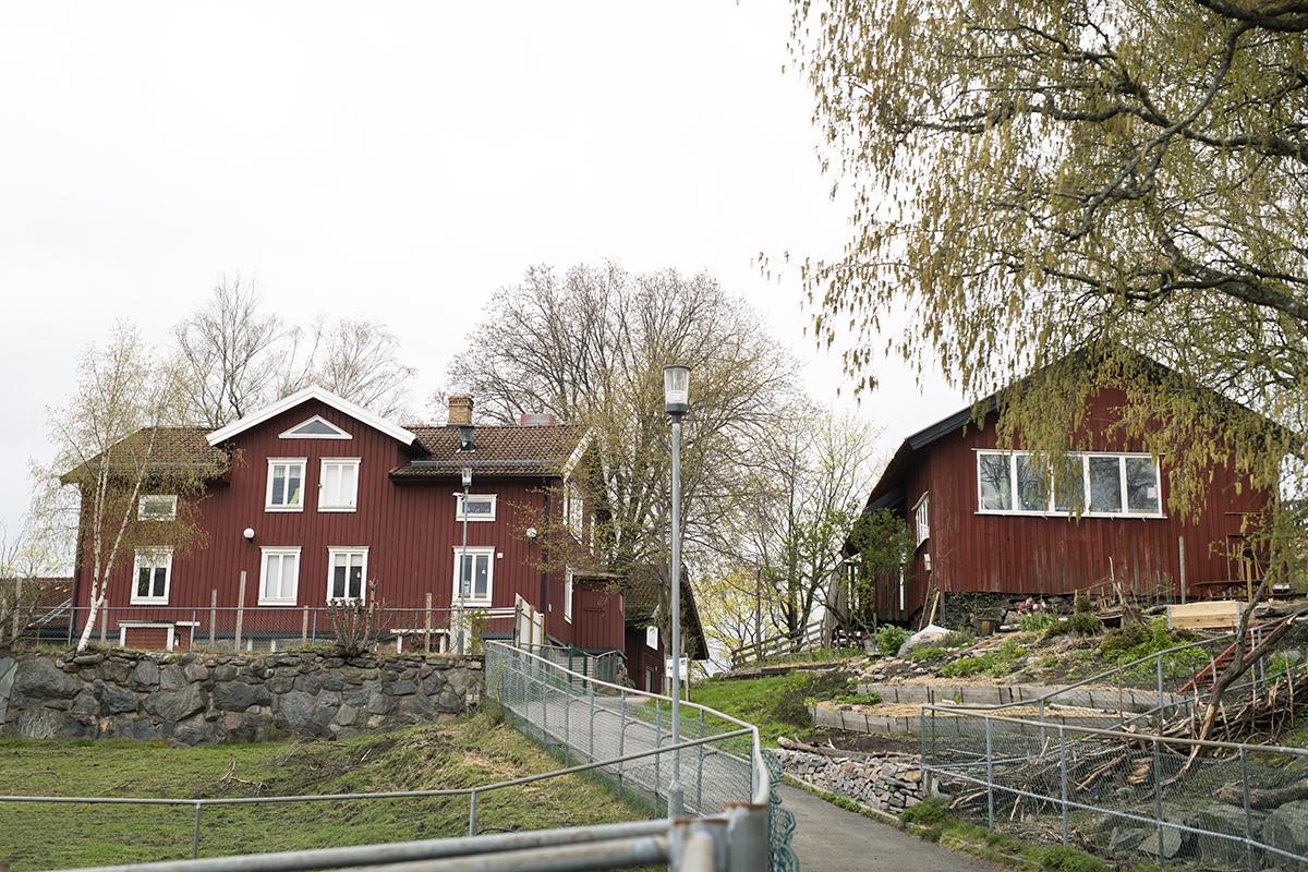 Lantgård. Rött hus med vita knutar.