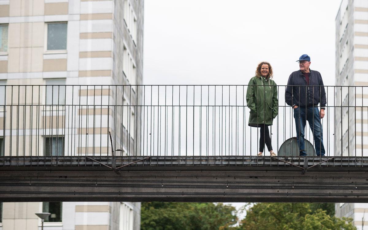 Monica Nilsson och Christer Jönsson, står på en bro i området Almgården i Malmö. Vita hus ramar in bron.