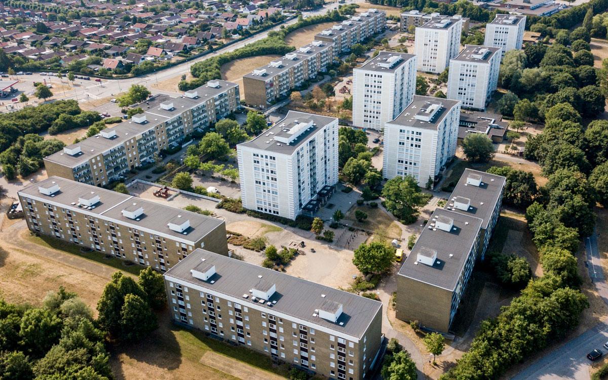 En flygbild över bostadsområdet Almgården i Malmö. På bilden syns sex vita höghus och sex lite lägre gulteglade flerfamiljshus.