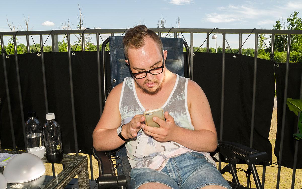 Anton sitter på sin balkong i gruppbostaden och tittar på sin mobiltelefon.