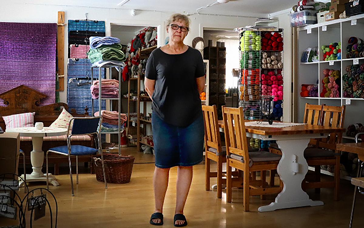 Åsa Andersson står mitt i sin affär. I bakgrunden syns bord, hyllor med garner samt textilier.