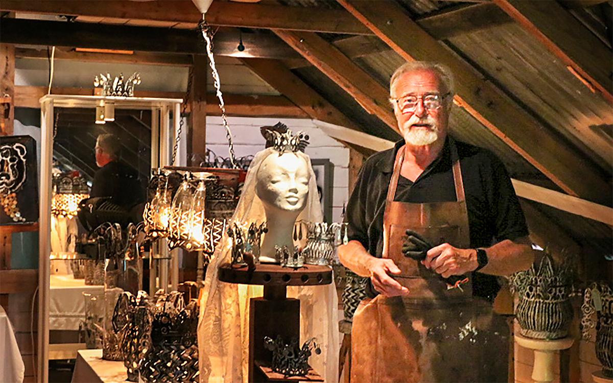 Björn Flinth står med ett förkläde i läder i sin ateljé, omgiven av sina konstföremål. I bakgrunden syns en spegel där han syns bakifrån