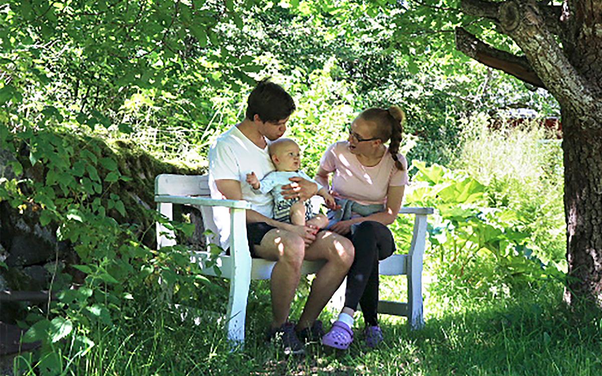 Elias, Liam och Ellen sitter i en soffa i trädgården. Solen strålar genom det gröna bladverket.