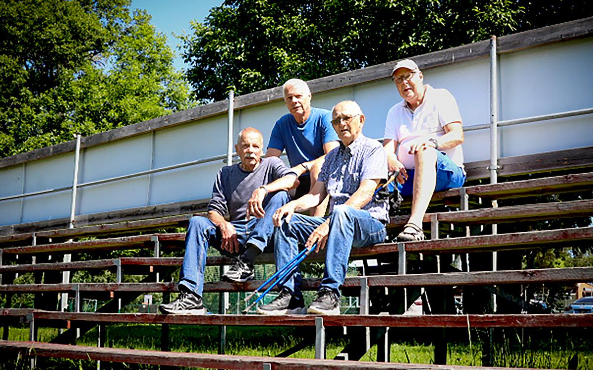 Fyra män som sitter på en läktare vid en idrottsplan. Det är soligt ute.