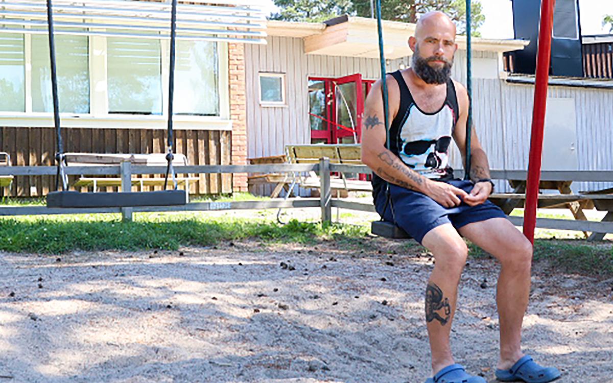 Per-Ola Gustavsson , iklädd shorts och linne, sitter i en gunga utanför skolan.