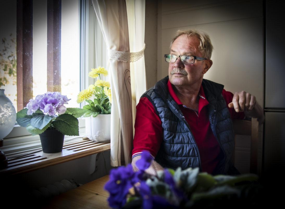 Roger Magnusson sitter vid köksbordet och tittar ut genom fönstret.