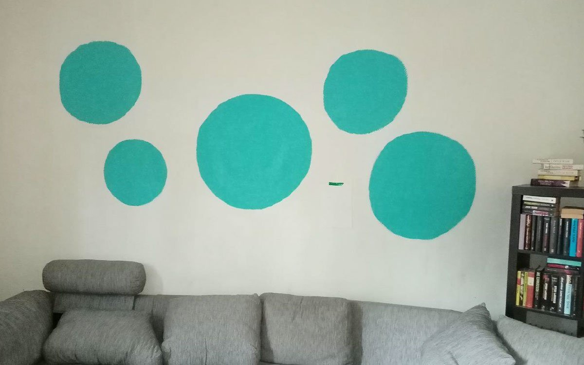 På väggen i vardagsrummet har en tidigare hyresgäst målat gröna bollar. är
