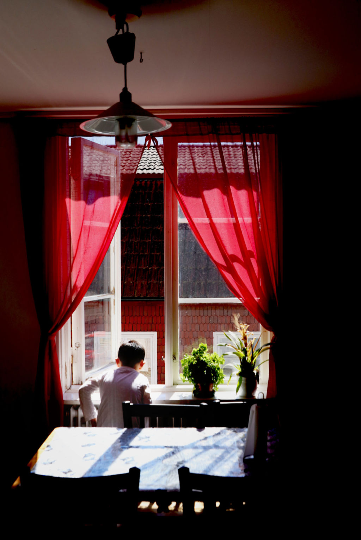 Ett barn tittar ut genom ett öppet fönster med röda gardiner