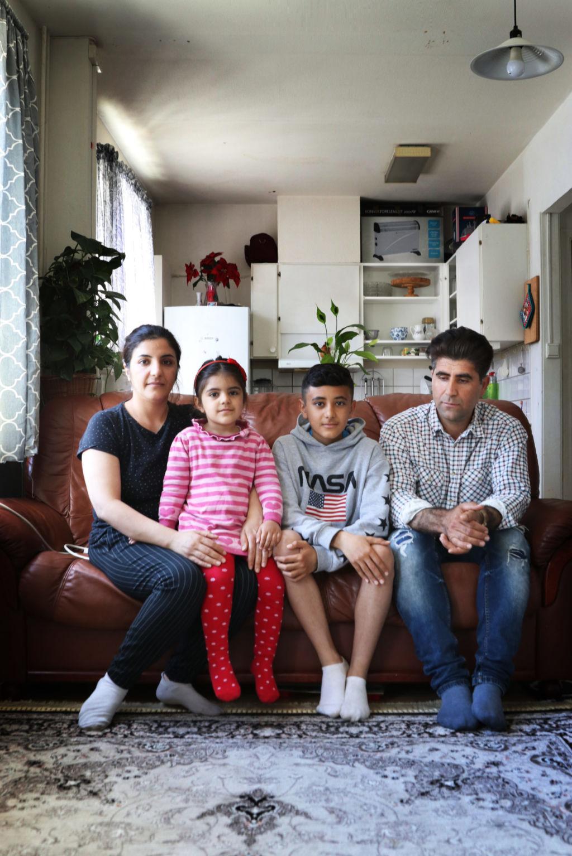 Familjeporträtt med en familj i en soffa i vardagsrummet. I bakgrunden syns köket.