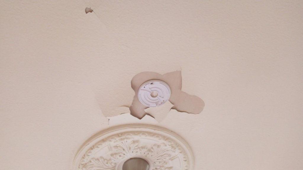 Brandvarnare som klistrats fast har förstört det målade innertaket i flera rum.