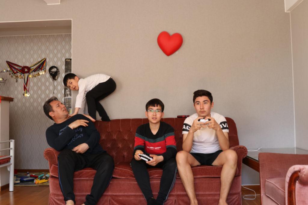 Tre barn och en pappa i en soffa.