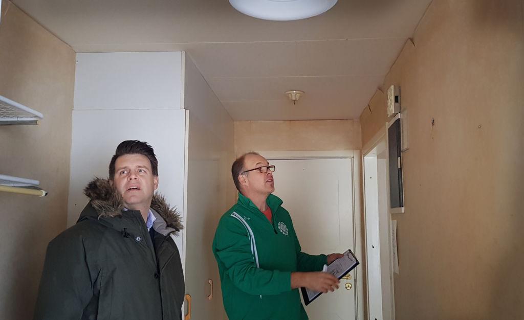 Två män undersöker slitaget i hallen på en lägenhet.